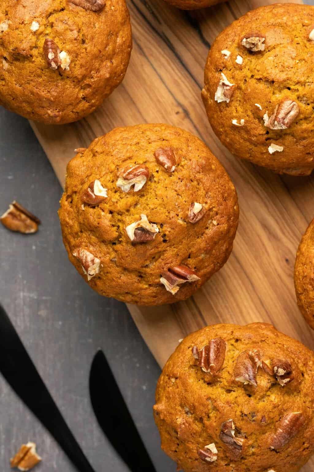 Vegan pumpkin muffins on a wooden board.