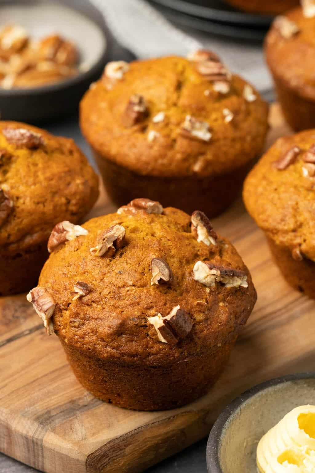 Pumpkin muffins topped with chopped pecans.