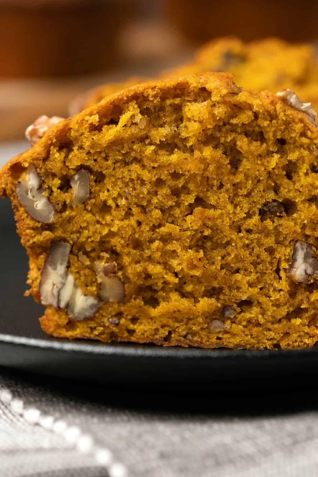 Vegan pumpkin muffin sliced in half on a plate.