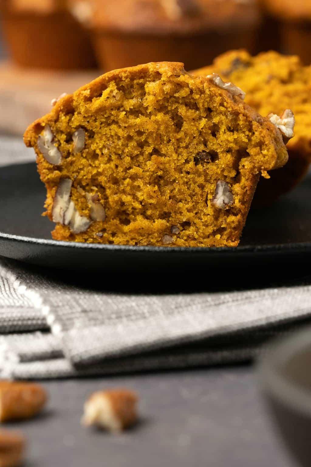 Pumpkin muffin cut in half on a black plate.