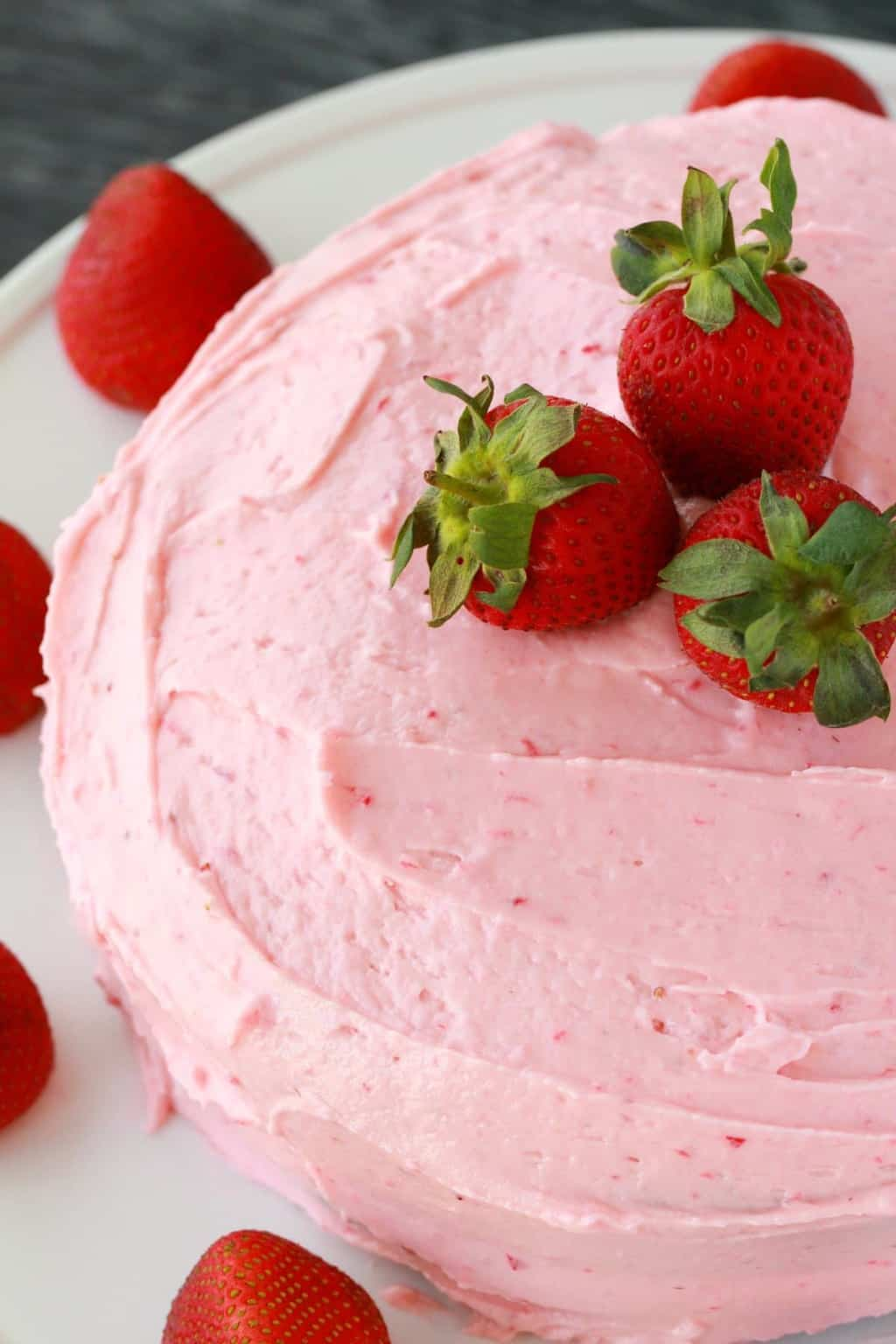 Light, fluffy and deliciously moist vegan strawberry cake with strawberry frosting. This pretty pink cake is packed with strawberry flavor and goodness. #vegan #lovingitvegan #strawberrycake #vegancake #dessert #dairyfree