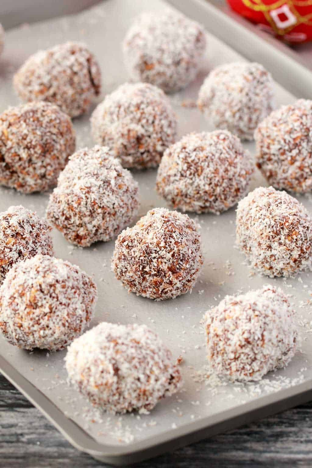 Chocolate snowballs on a parchment lined baking tray.