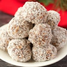 Chocolate coconut snowballs stacked up on a white plate.