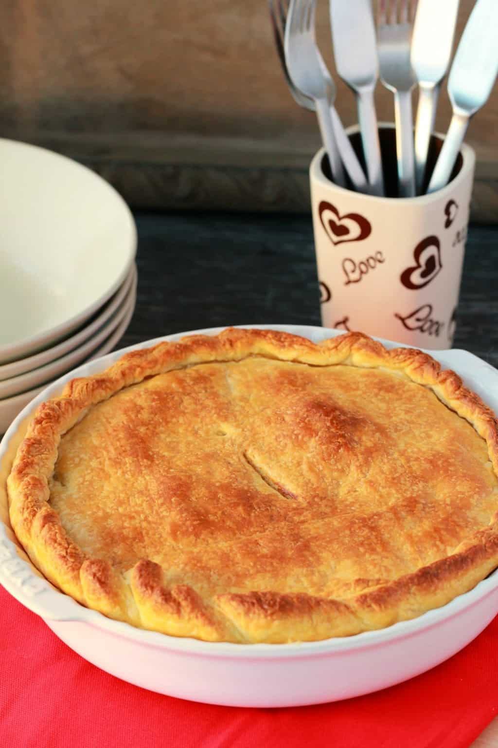 Freshly baked pot pie in a white pie dish.