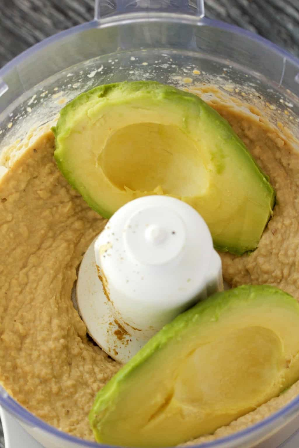 Hummus in a food processor with avocados on top.