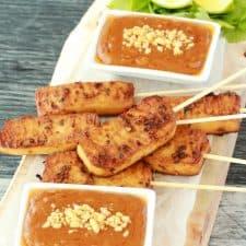 Tofu satay and peanut sauce on a wooden board.
