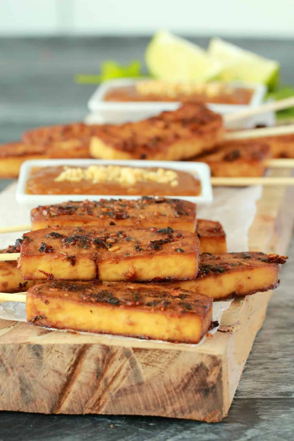 Baked tofu satay on a wooden board with peanut sauce in a white dish.