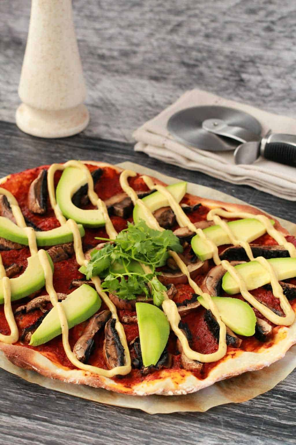 Homemade thin-crust pizza with tomato sauce, black mushrooms, sliced avocado and drizzled cashew cheese, on parchment paper with a napkin and pizza cutter in the background