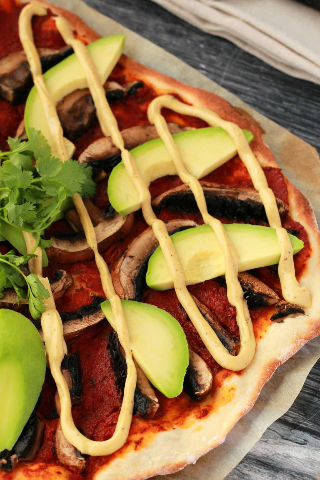 Close up side on shot of homemade pizza with tomato sauce, black mushrooms, sliced avocado and drizzled cashew cheese on parchment paper, a napkin in the background