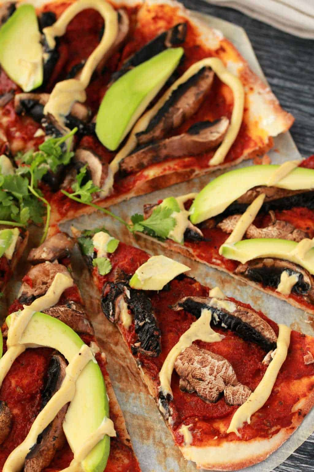 Close up overhead shot of a homemade sliced pizza, topped with tomato sauce, black mushrooms, sliced avocado and cashew cheese