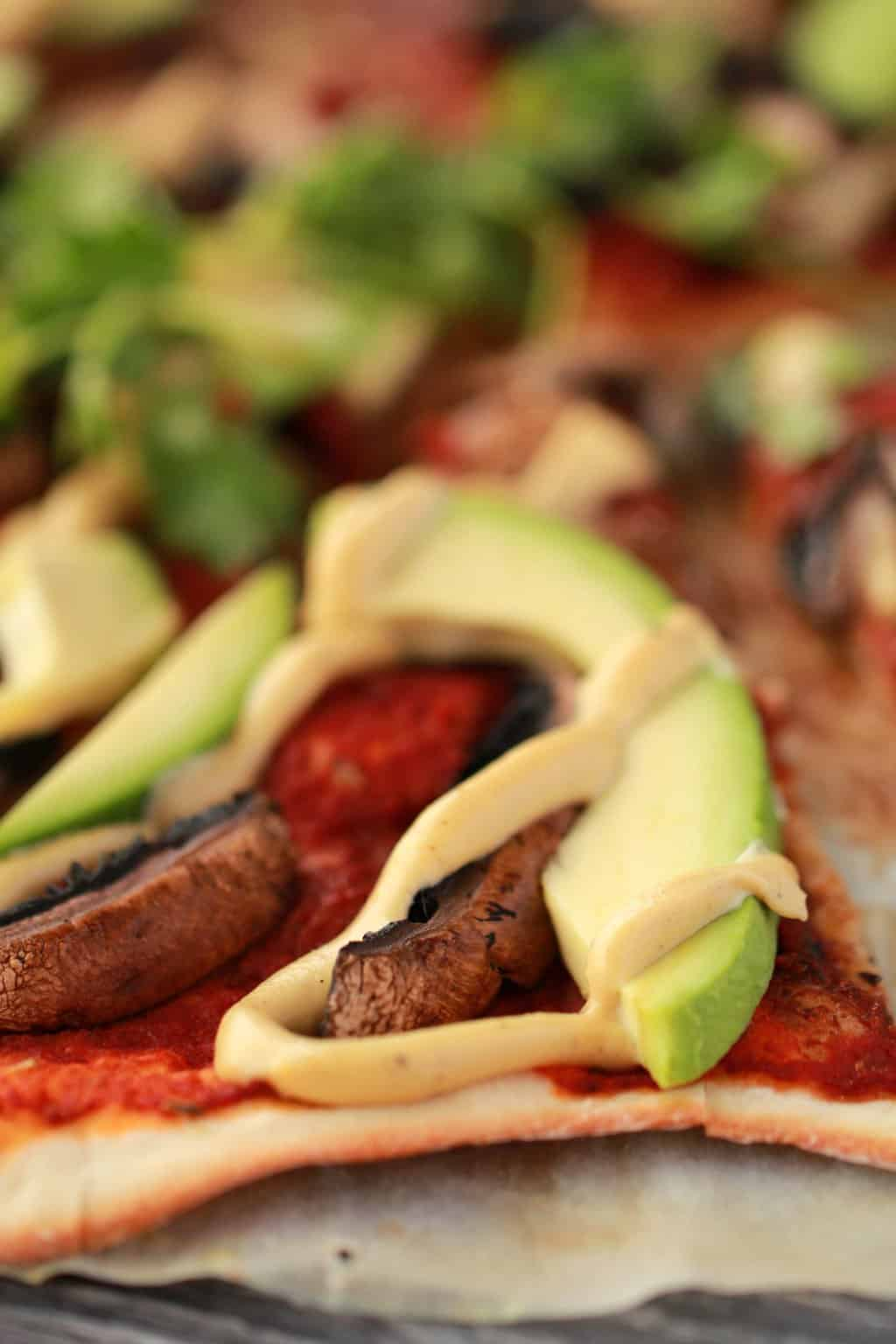 Close up shot of homemade pizza topped with tomato sauce, black mushrooms, sliced avocado and cashew cheese