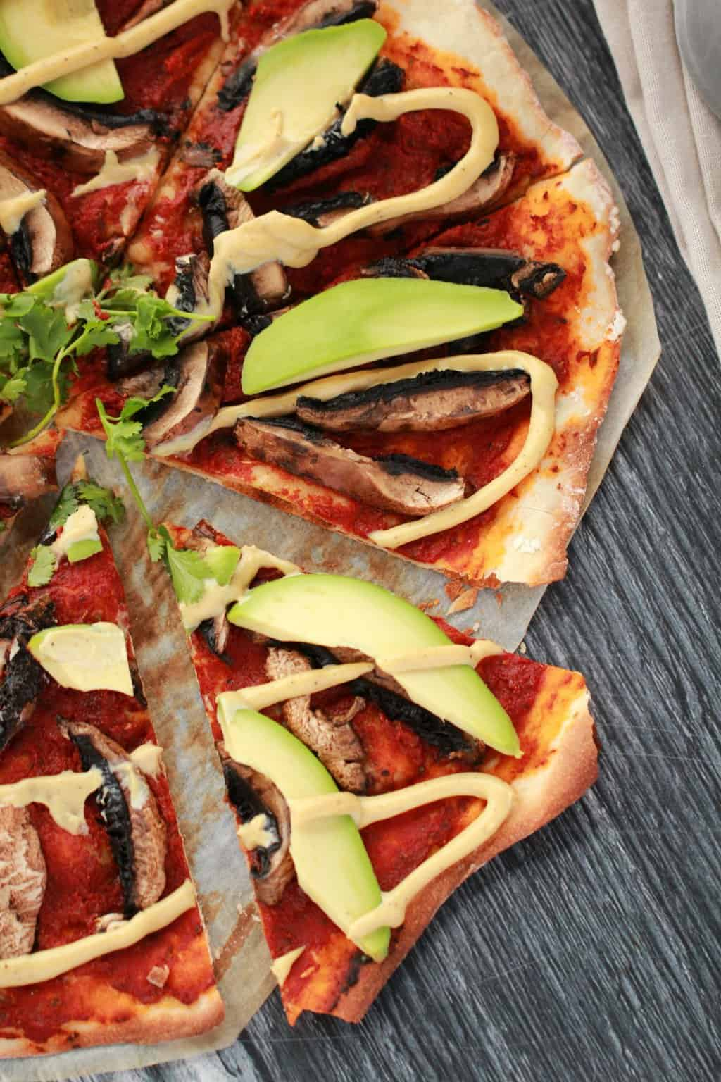Sliced homemade pizza topped with tomato sauce, black mushrooms, sliced avocado and drizzled cashew cheese on parchment paper
