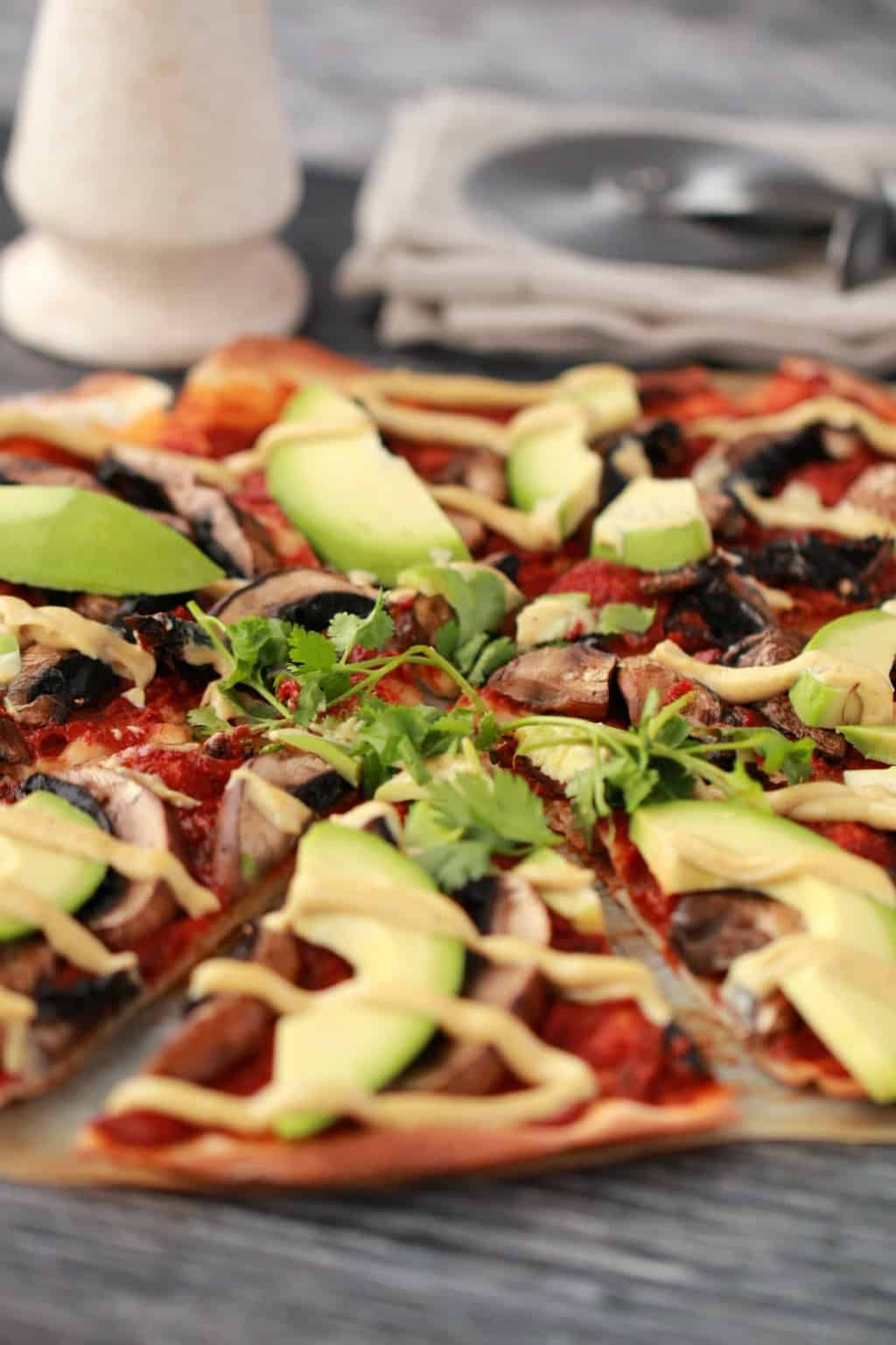 Sliced homemade pizza topped with tomato sauce, black mushrooms, sliced avocado and drizzled cashew cheese, with a napkin and pizza cutter in the background