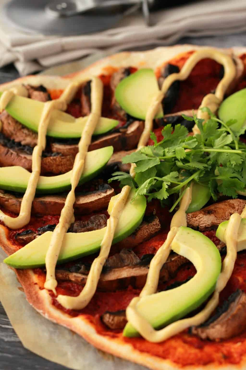 Homemade pizza with tomato sauce, black mushrooms, sliced avocado and drizzled cashew cheese on parchment paper