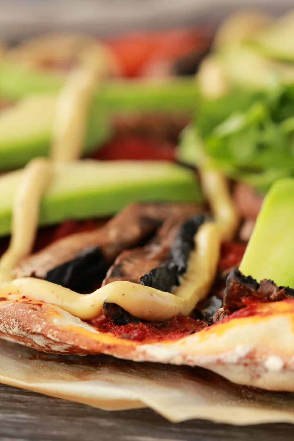 Close up of homemade pizza with tomato sauce, black mushrooms, avocado and drizzled cashew cheese