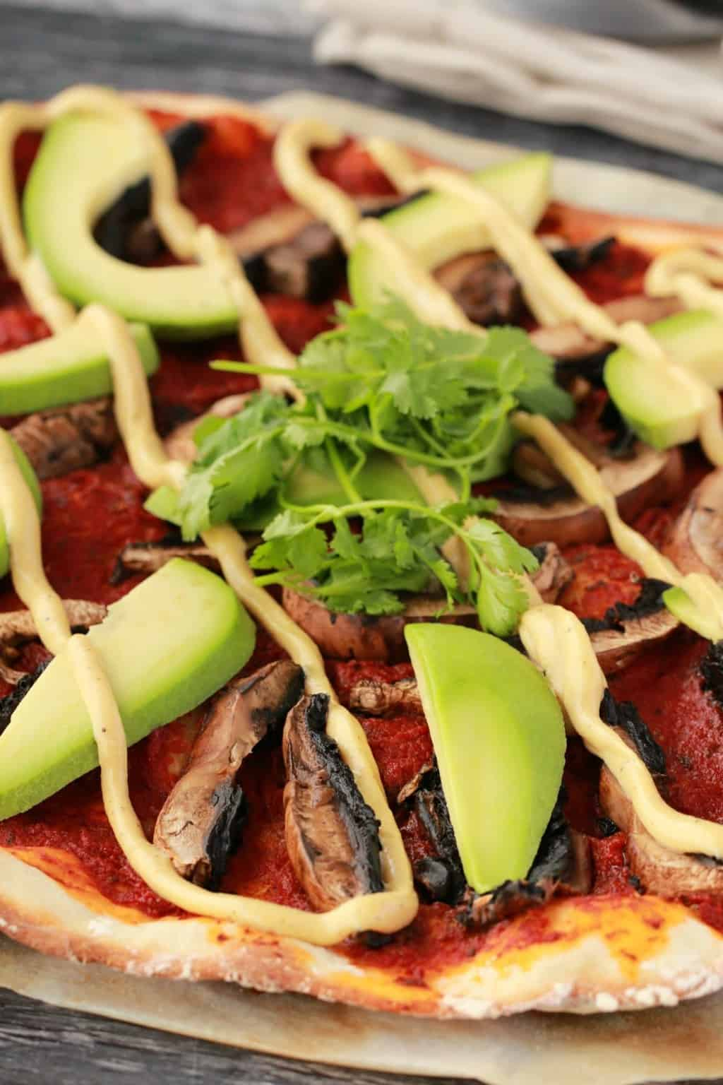 Homemade pizza with tomato sauce, black mushrooms, sliced avocado and a drizzle of cashew cheese