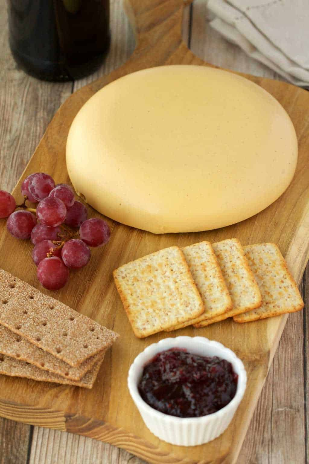 Wheel of vegan cashew cheese on a cheese board with crackers, grapes and jam.