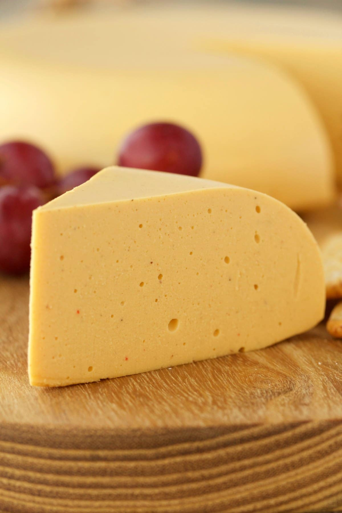 Large wedge of vegan cheese on a cheese board with grapes and crackers.
