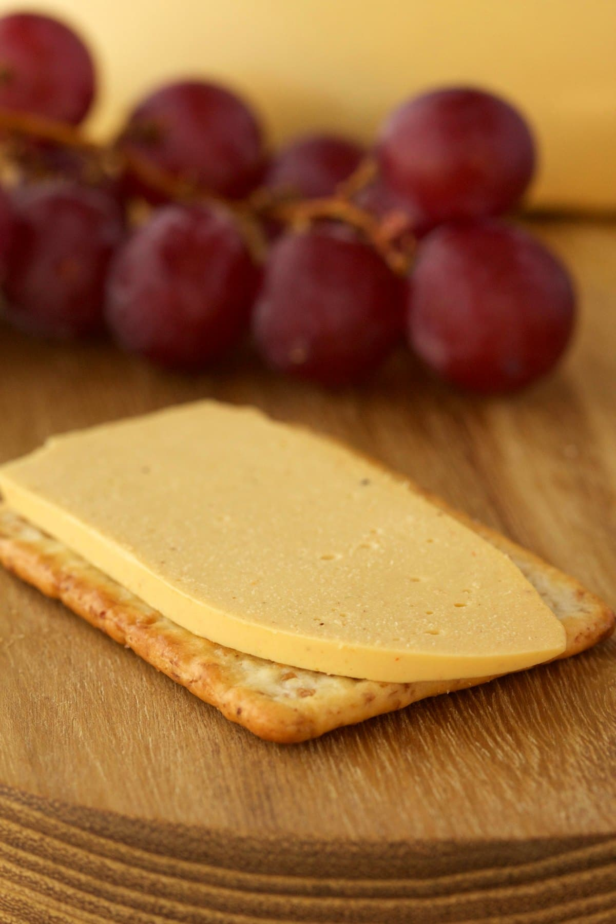 A slice of vegan cashew cheese on a cracker.