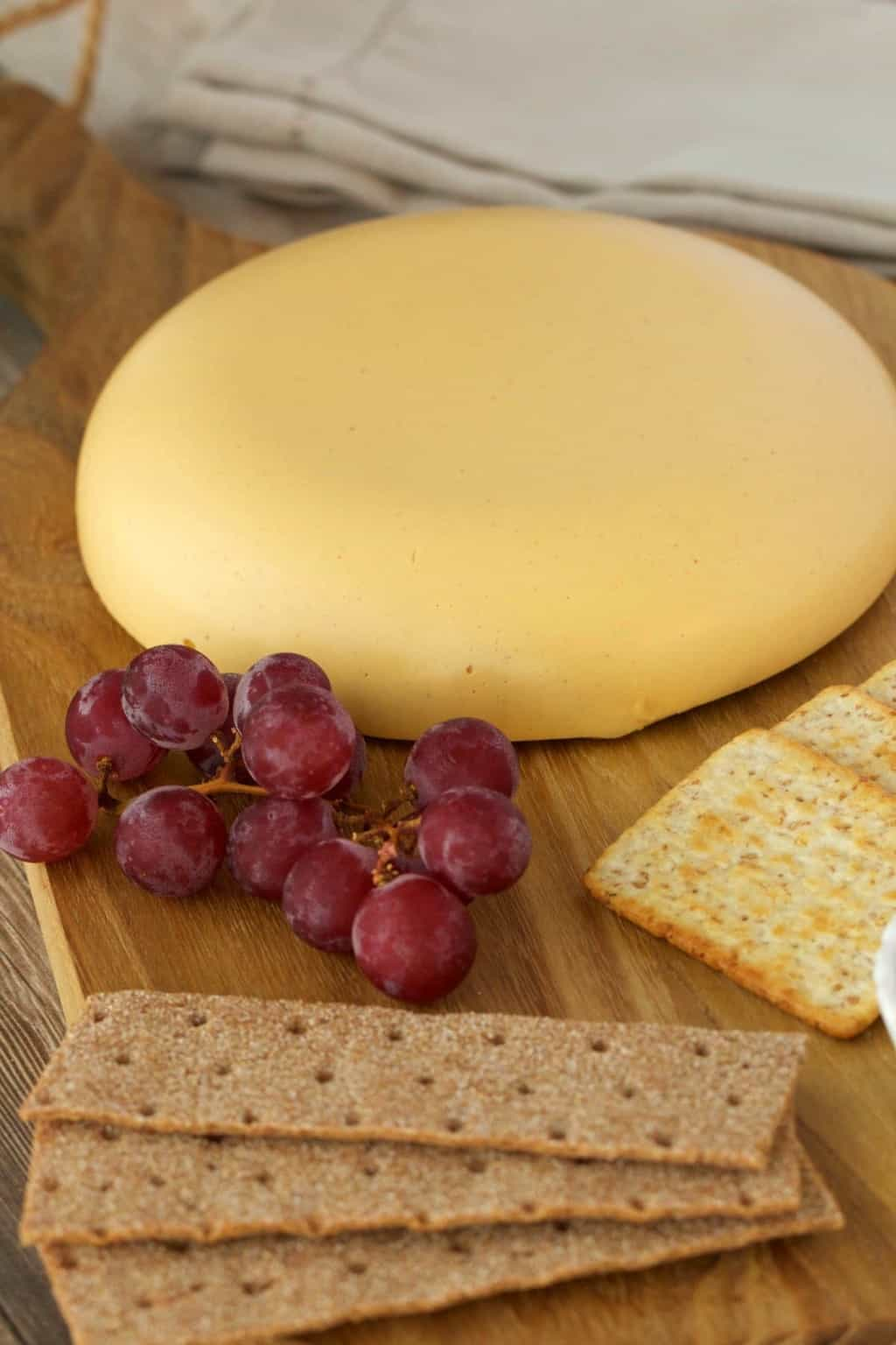 Wheel of vegan cashew cheese on a cheese board with red grapes and crackers.