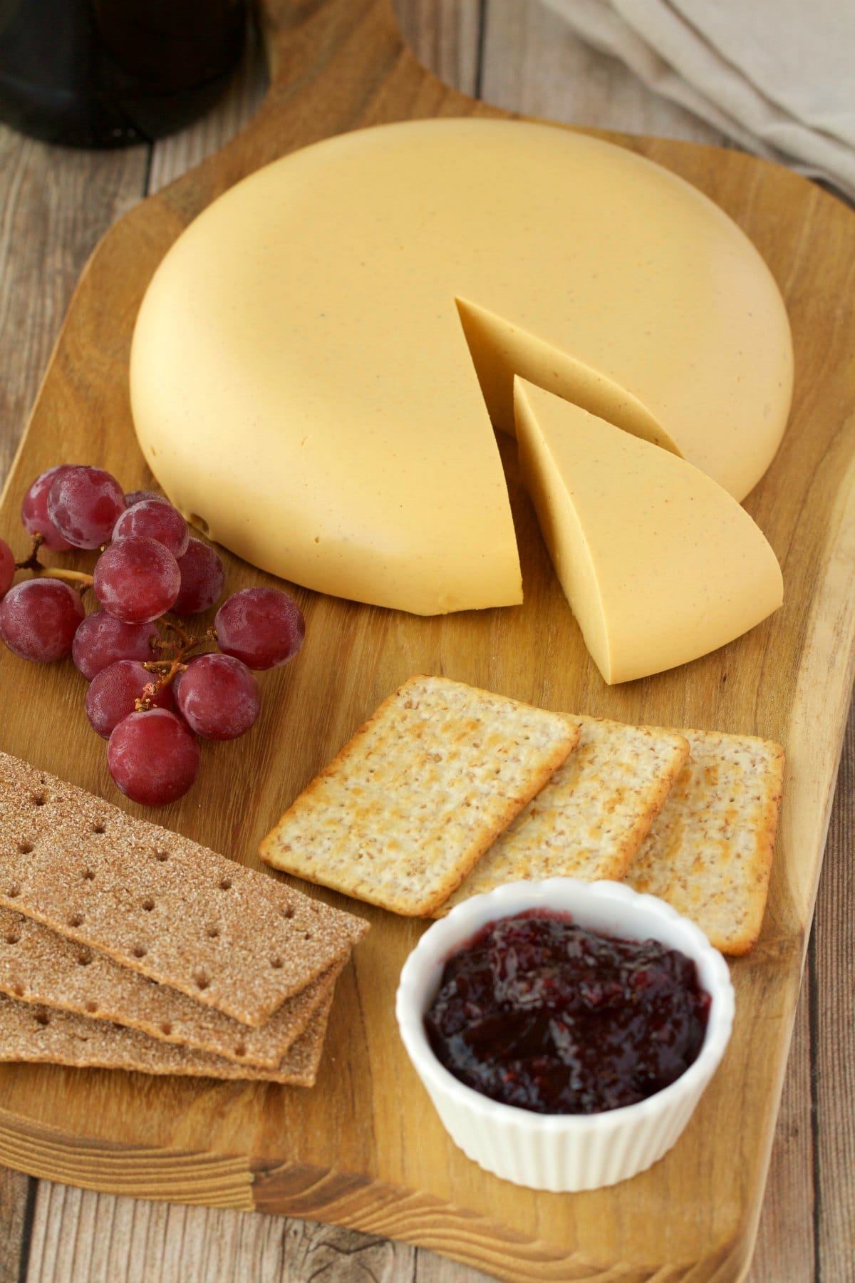 Wheel of vegan cashew cheese on a cheeseboard with crackers, grapes and jam.