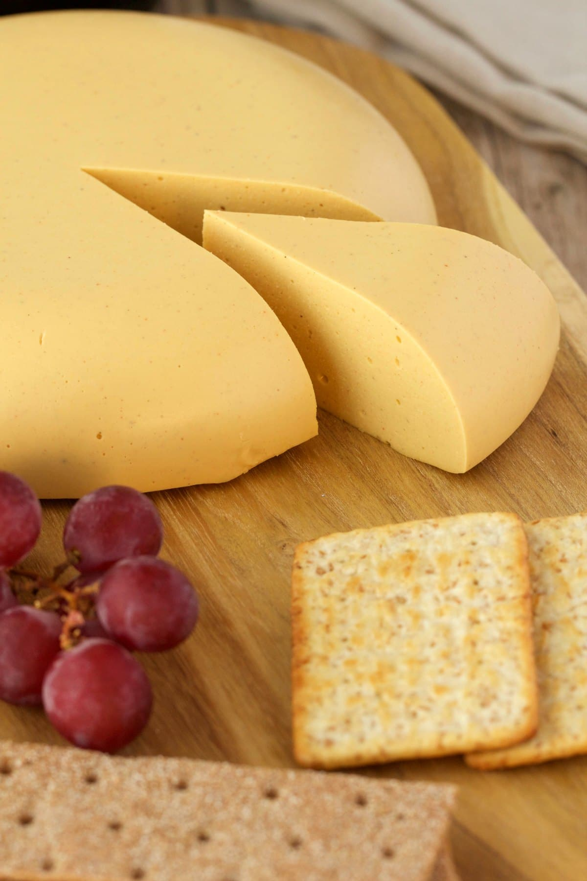 Vegan cheese on a cheese board with red grapes and crackers.