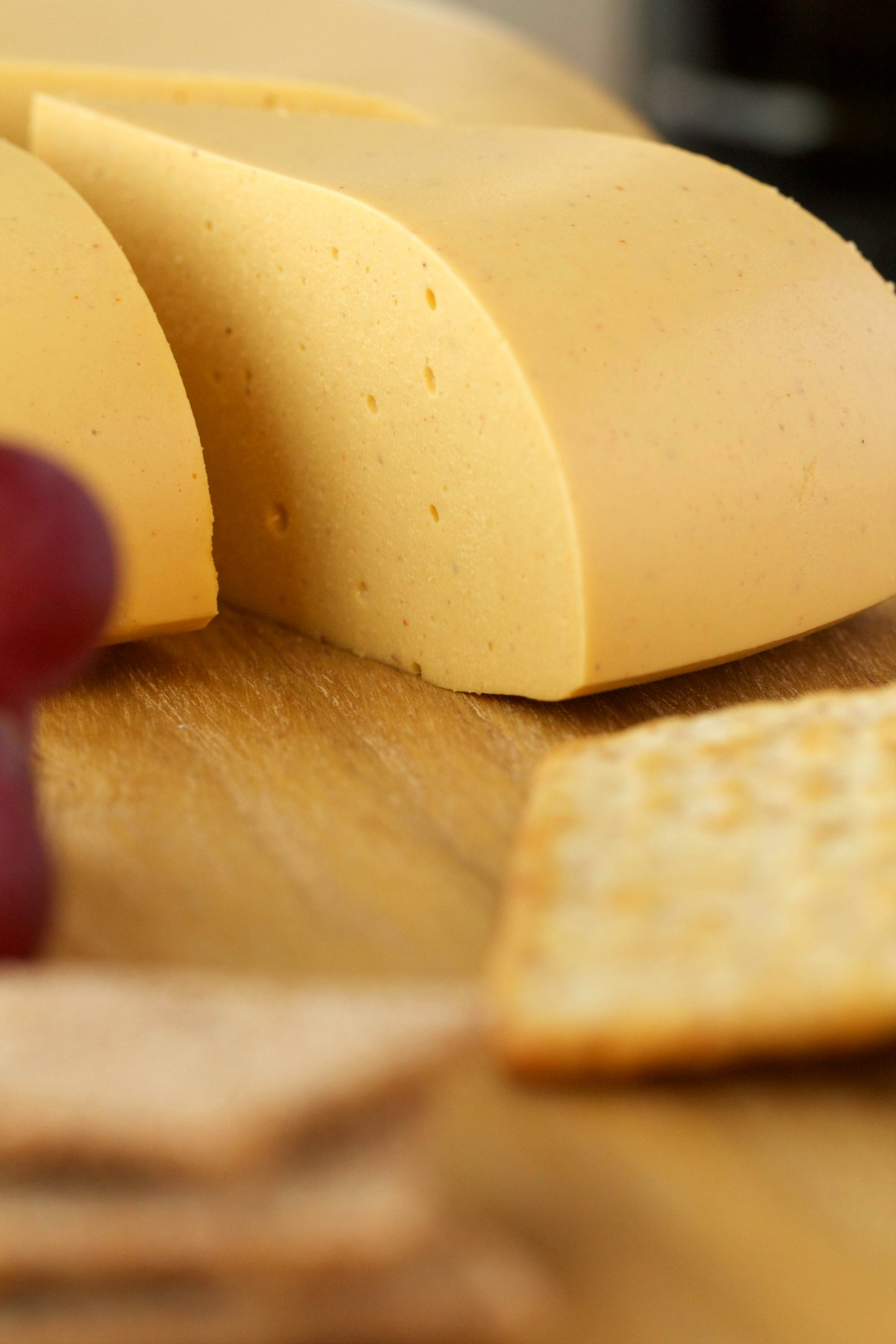 Sliced wheel of cashew cheese on a cheese board with crackers and grapes.