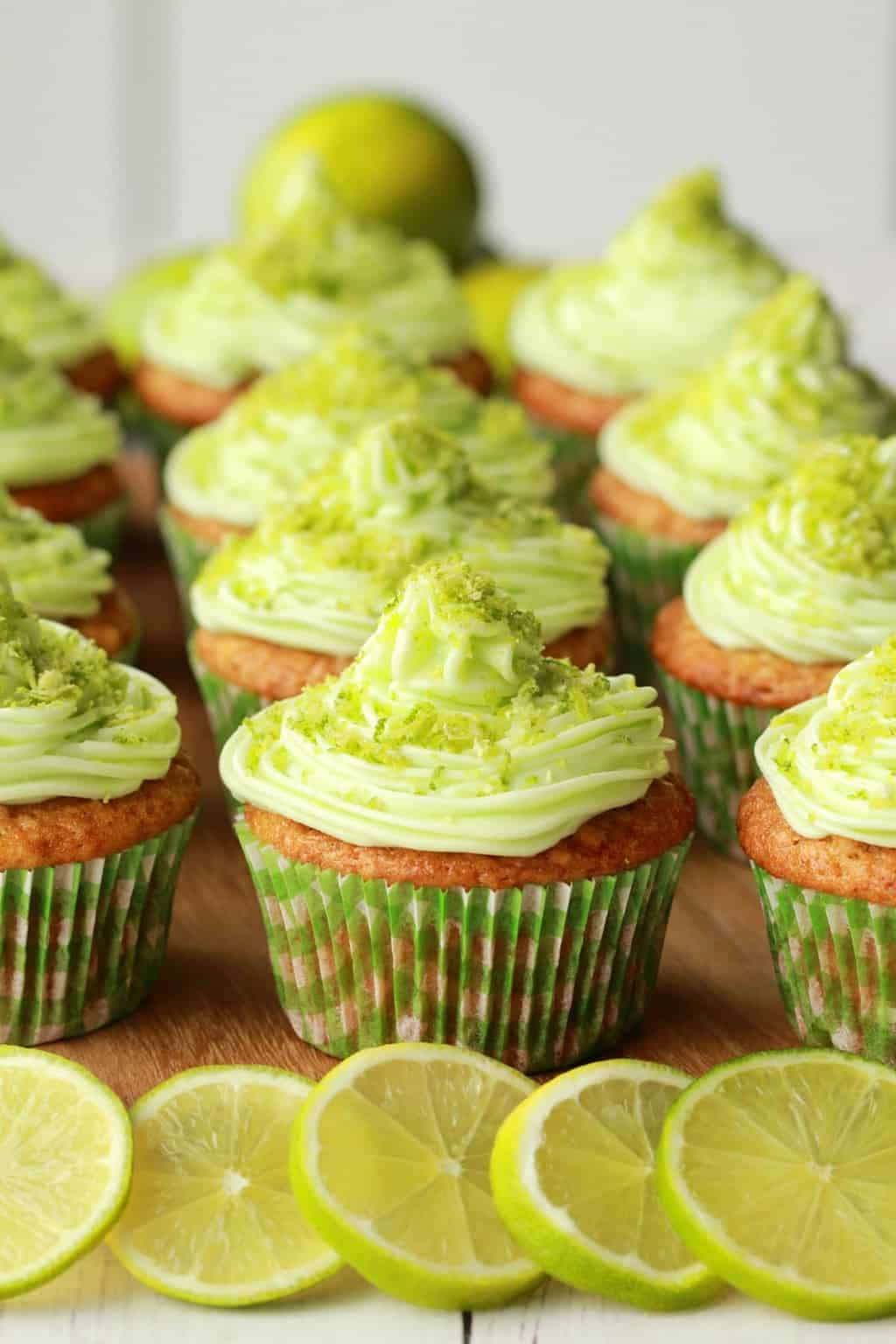 Vegan Key Lime Cupcakes on a wooden board with whole limes in the background and lime slices in the foreground