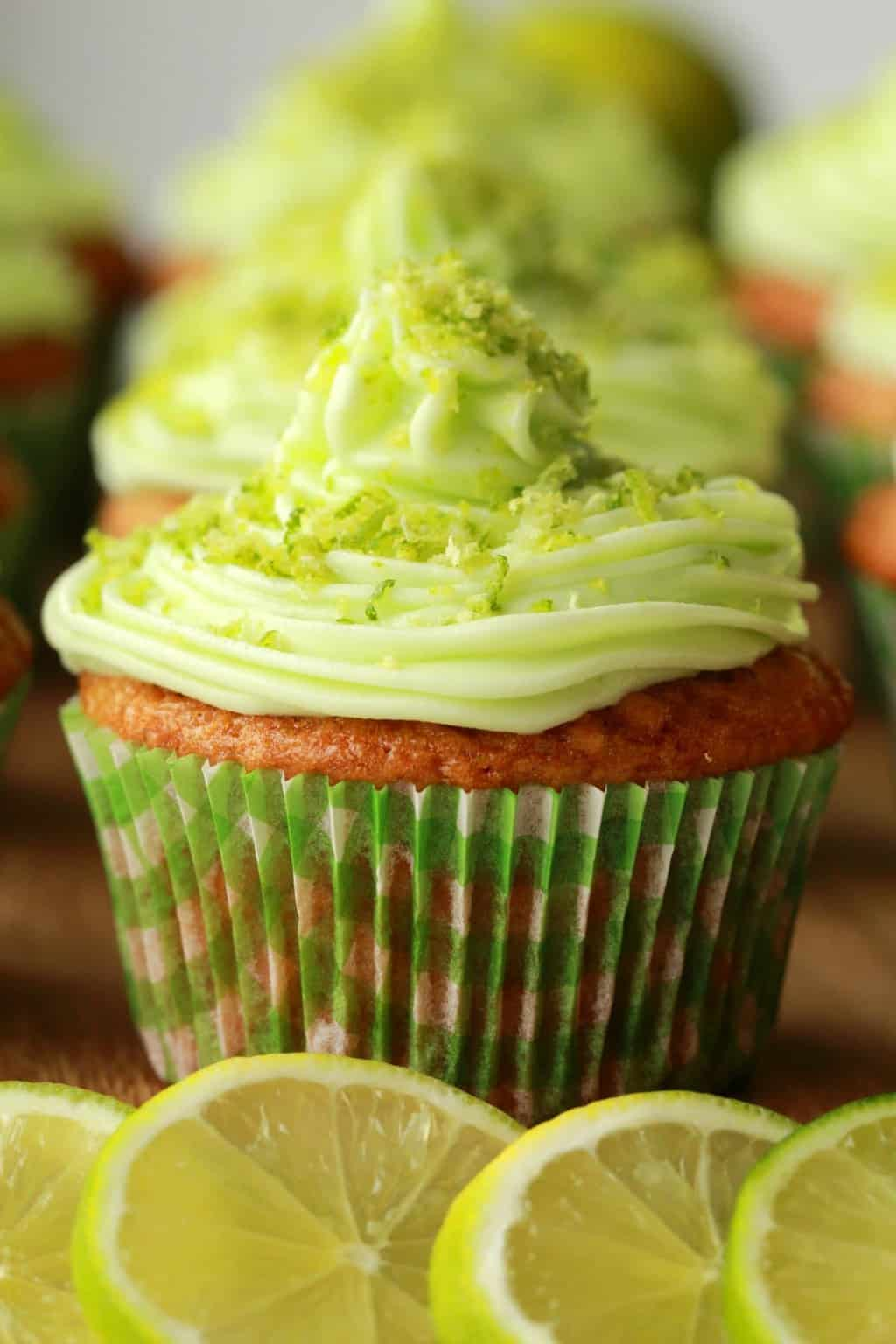 Close up of Vegan Key Lime Cupcake on wooden board with lime slices in the foreground