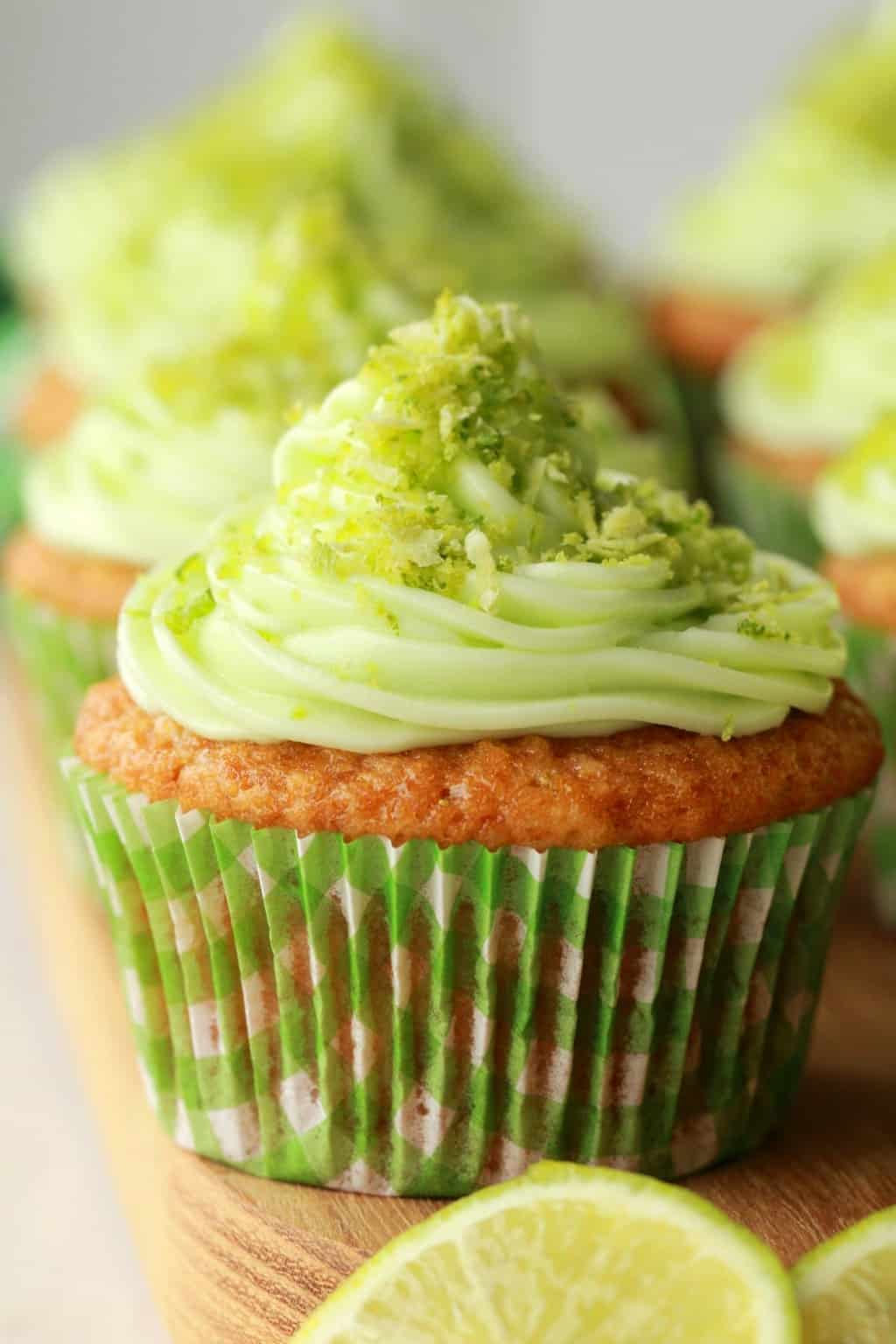 Vegan Key Lime Cupcakes close up with lime slices in the foreground