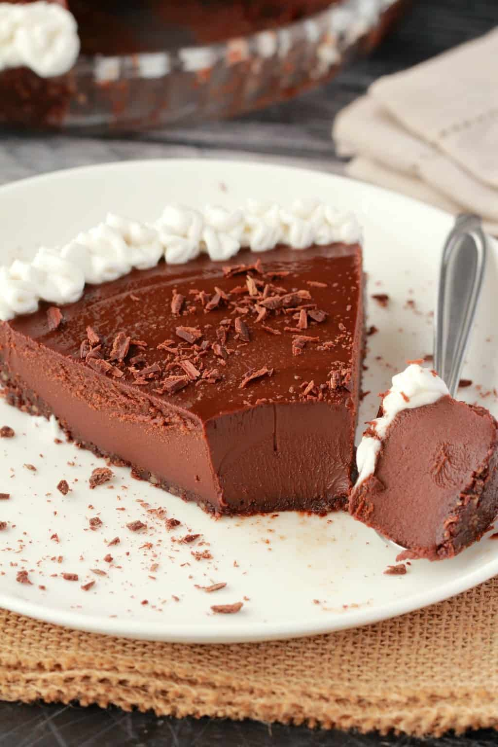Vegan Chocolate Pie slice on a white plate. A bite-sized portion of pie on a spoon next to it.
