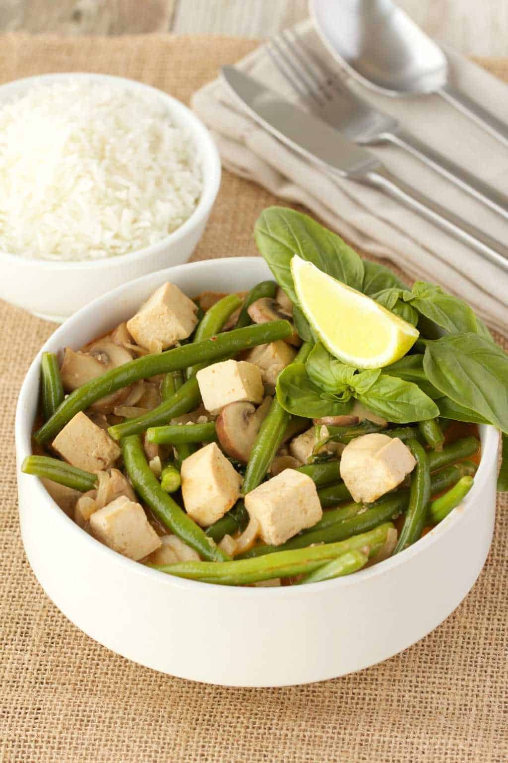Thai red curry with green beans and tofu in a white bowl, a bowl of rice, cutlery and a napkin on the side.