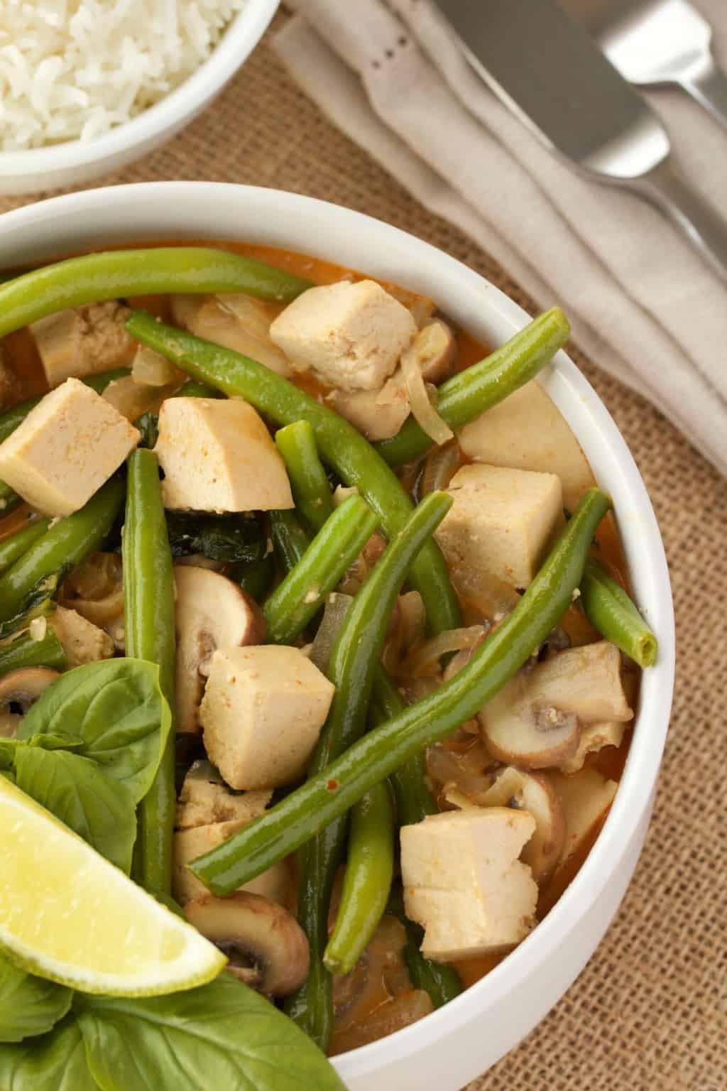 Thai red curry with green beans and tofu in a white bowl, a napkin and cutlery on the side.