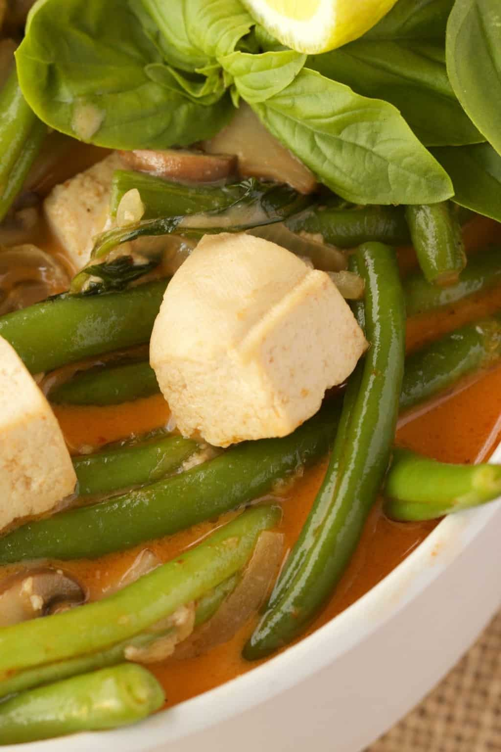 Super close up shot of thai red curry with green beans in a white bowl.