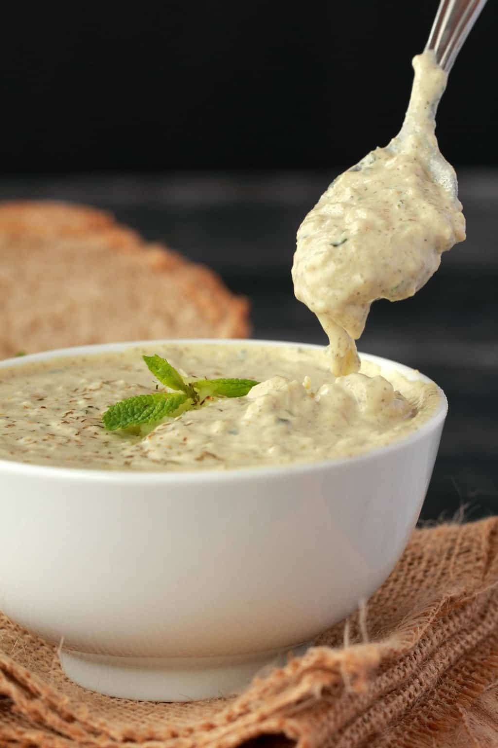 A spoonful of vegan tzatziki over a white bowl filled with tzatziki, sliced bread in the background.