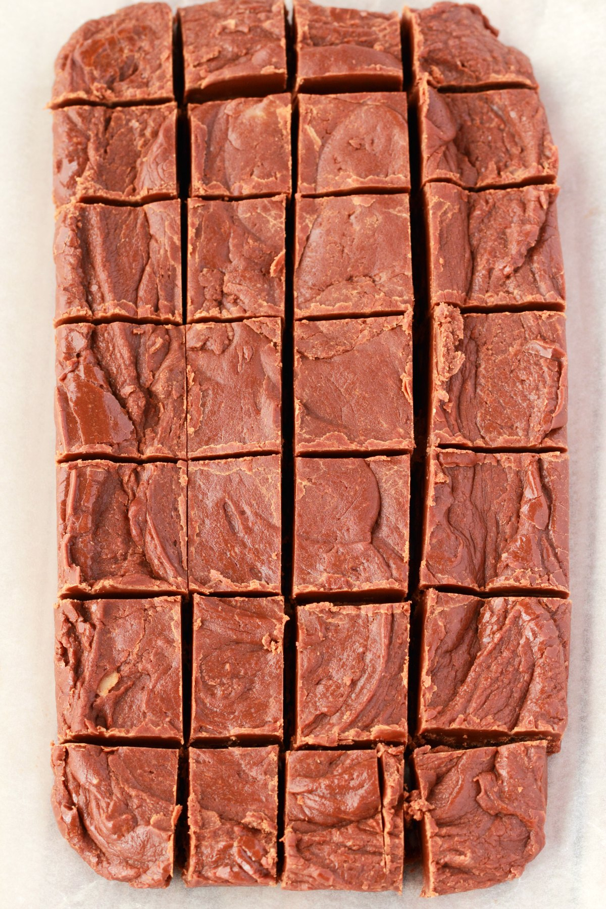 Dairy Free Fudge cut into squares, on parchment paper.
