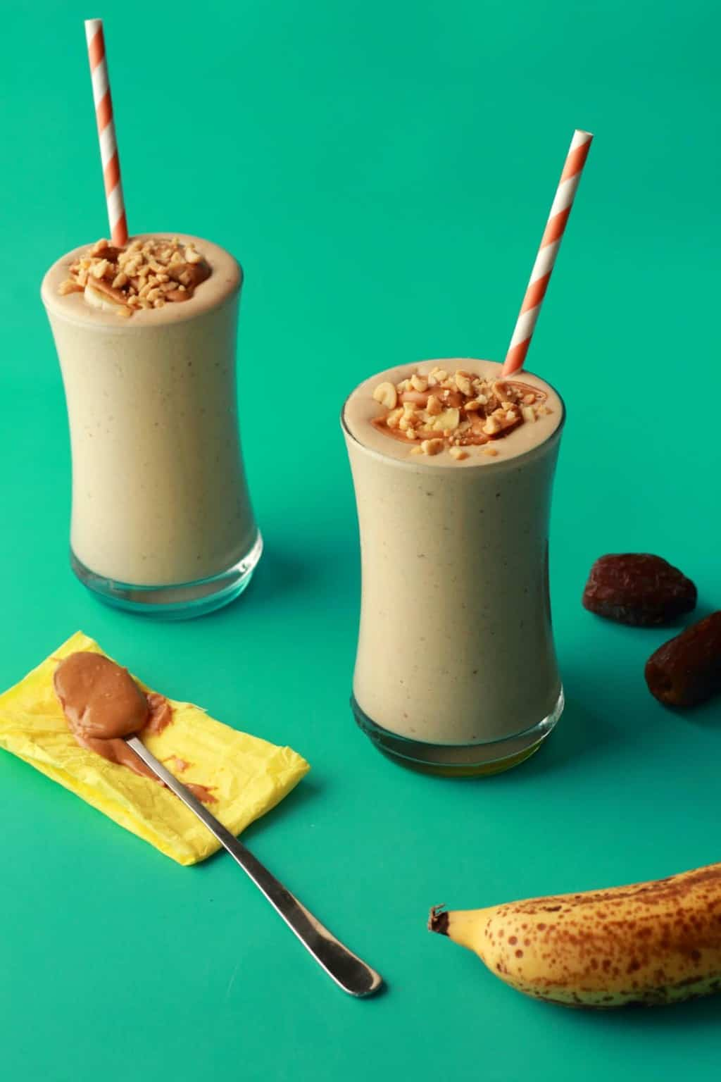 Peanut Butter Banana Smoothie on a green background with medjool dates, a banana and a spoonful of peanut butter.
