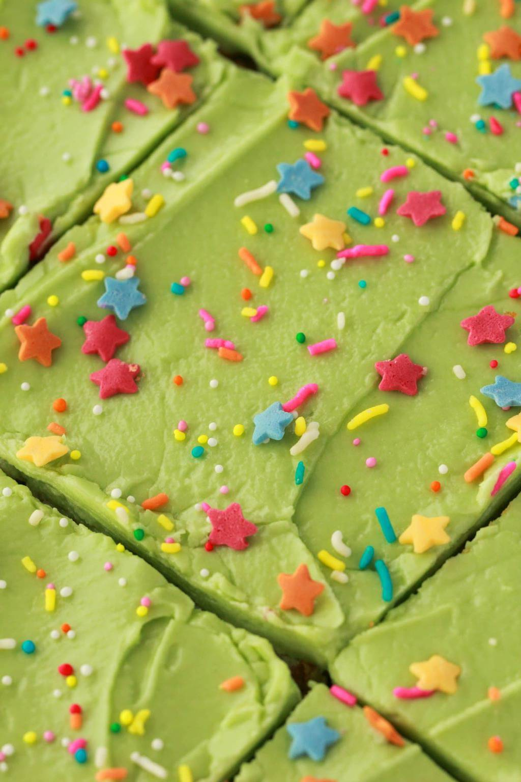 Close up overhead shot of vanilla sheet cake with green frosting and sprinkles.