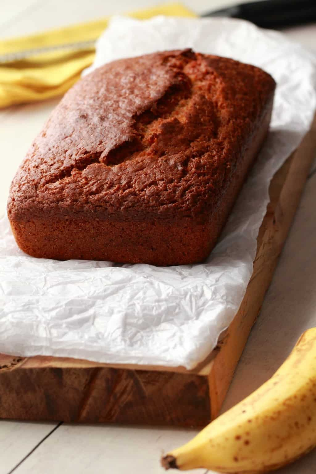 Vegan Banana Bread on parchment paper, a yellow napkin in the background.