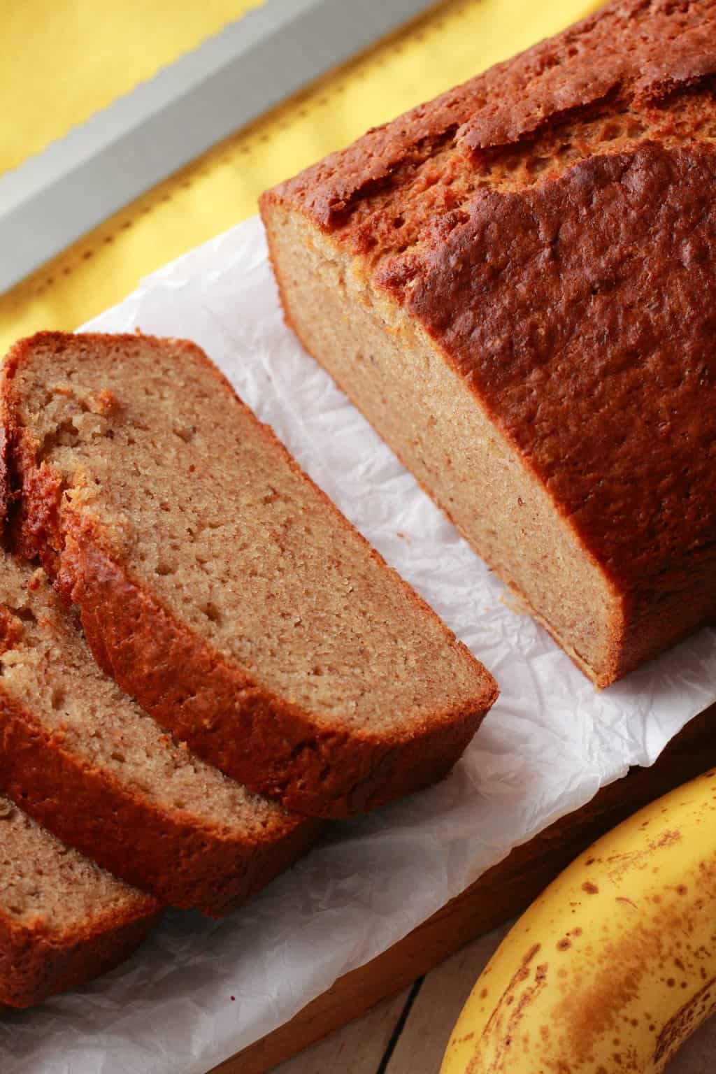 Sliced Vegan Banana Bread on parchment paper, a banana in the foreground.