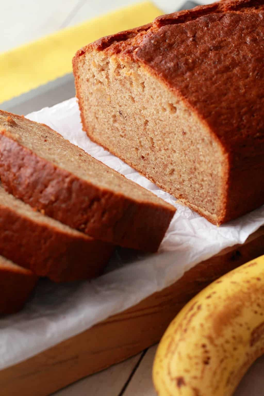 Sliced Vegan Banana Bread on parchment paper, a yellow napkin in the background.