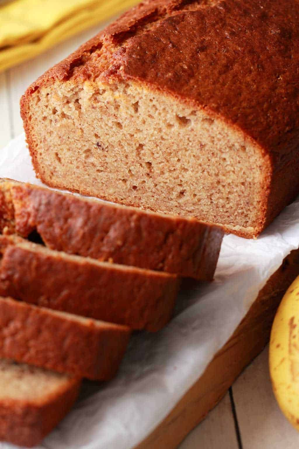 Sliced Vegan Banana Bread with a yellow napkin in the background.
