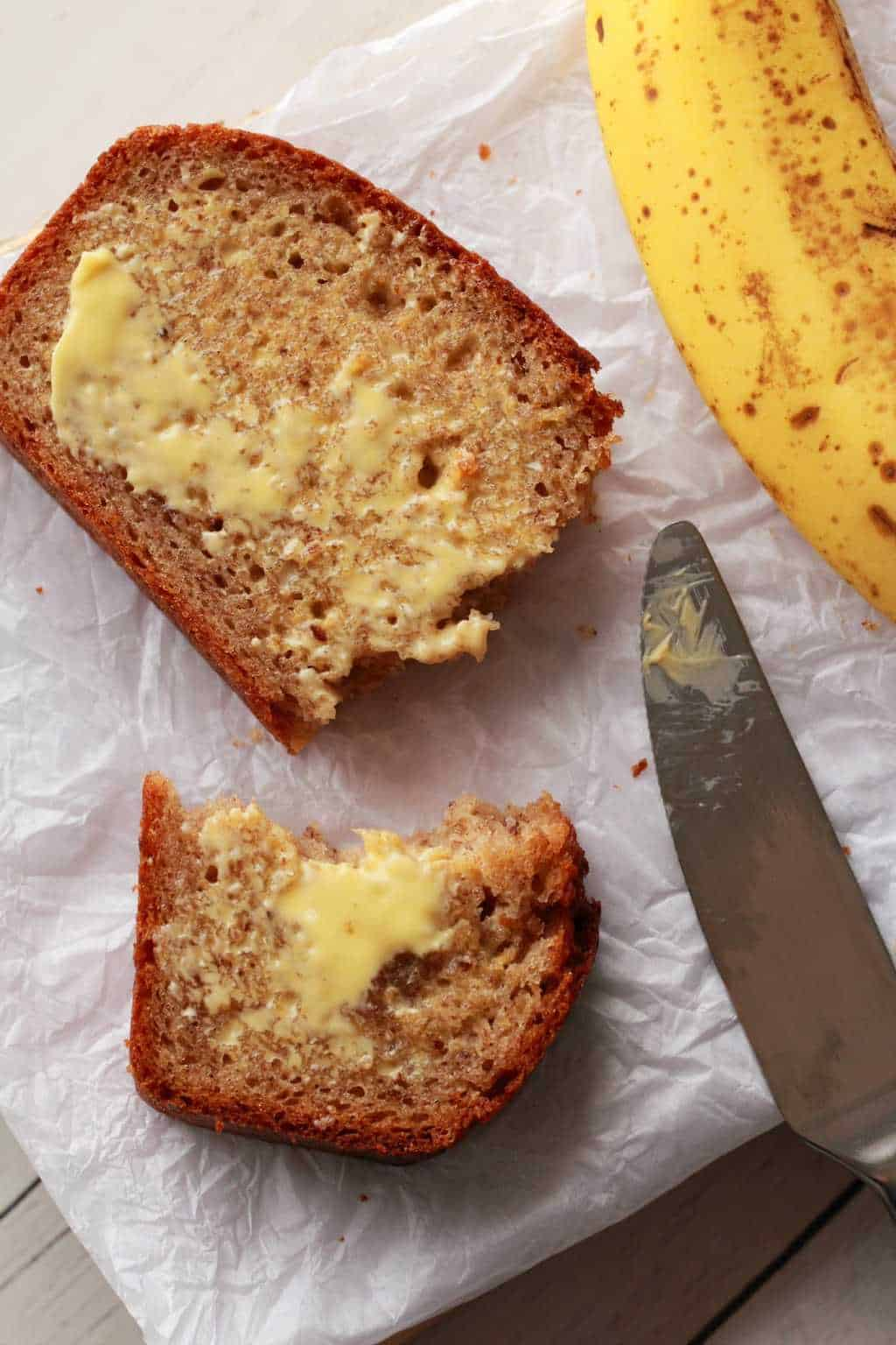 A slice of Vegan Banana Bread, broken in half and buttered. A butter knife and a banana alongside it.