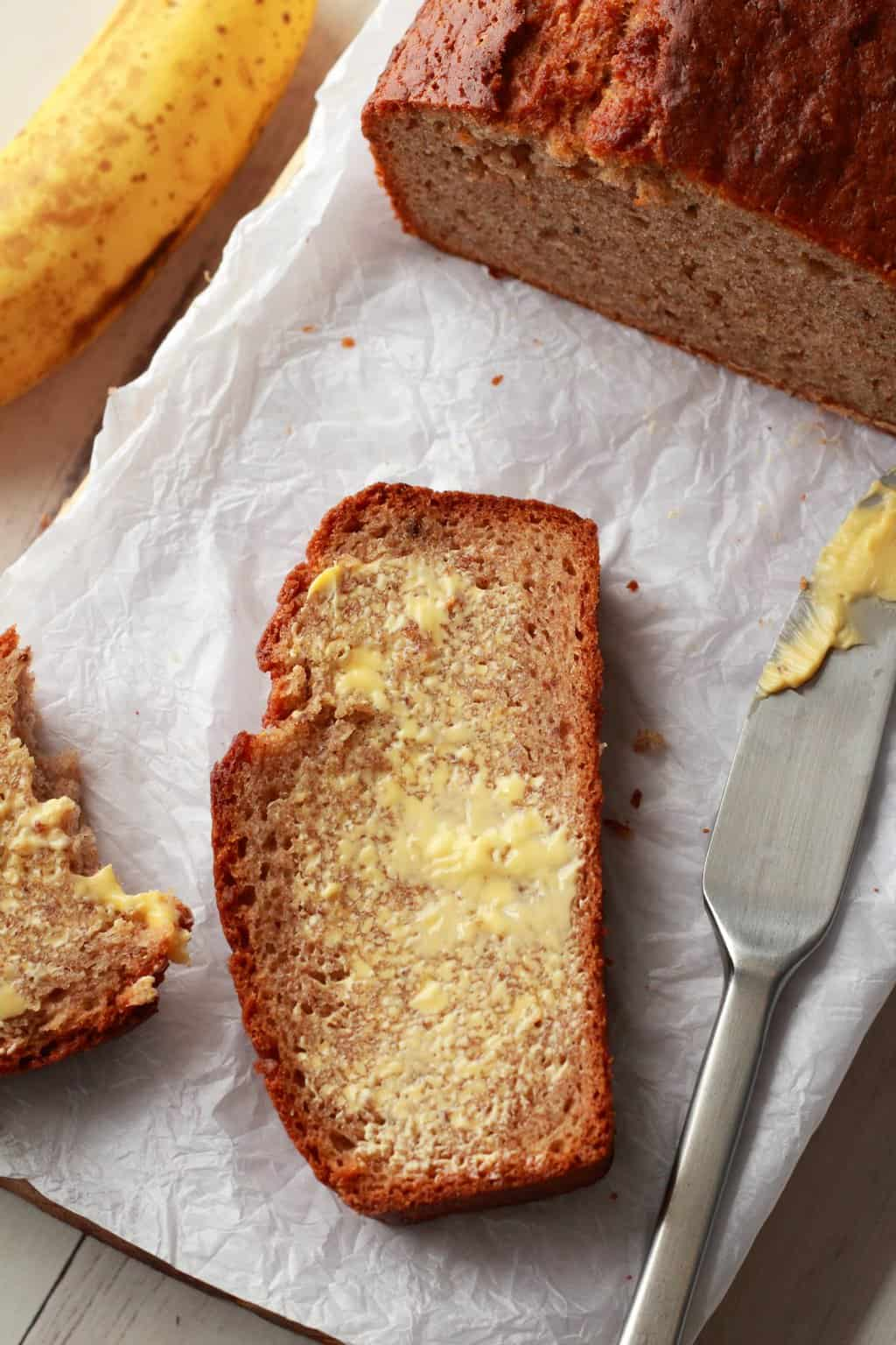 Sliced and buttered vegan banana bread with a butter knife next to it.