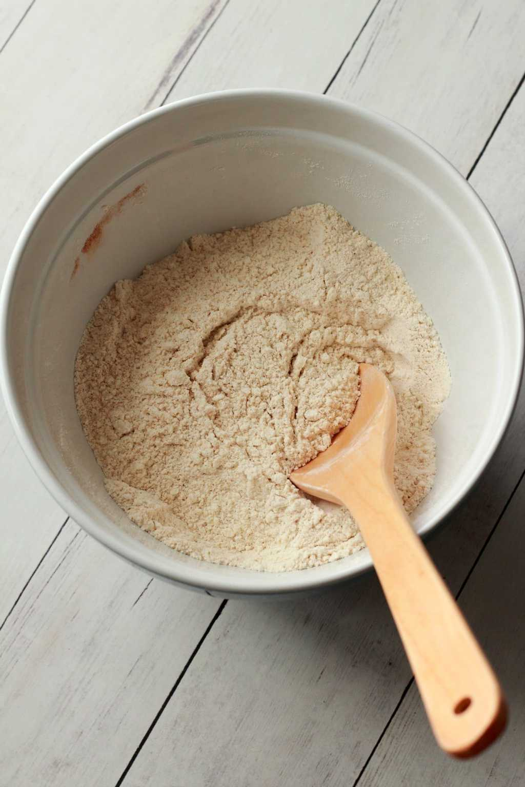 Flour, sugar and other dry ingredients in a mixing bowl with a wooden spoon.