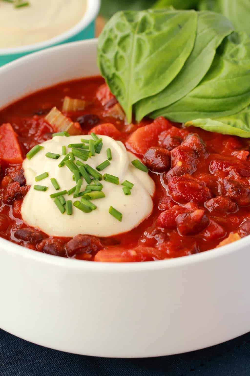 Vegan Chili in a white bowl with a dollop of cashew cream and chopped chives on top and fresh basil leaves on the side.