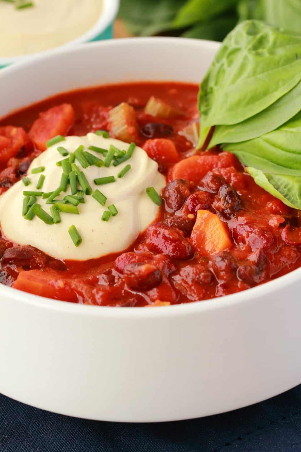 Vegan Chili in a white bowl with a dollop of cashew cream on the top and chopped chives, fresh basil leaves on the side.