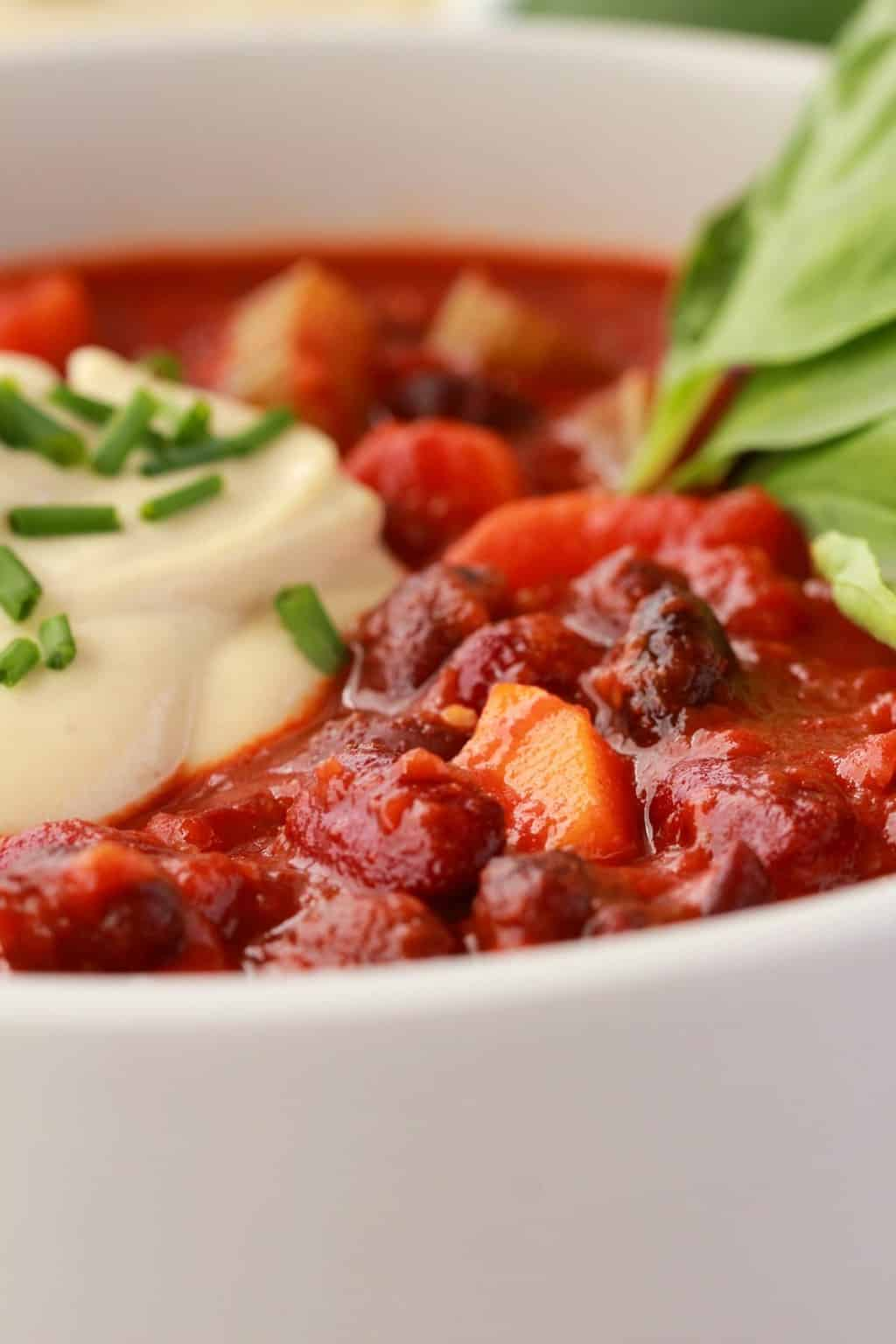 Vegan Chili in a white bowl with a dollop of cashew cream on top and chopped chives, fresh basil leaves on the side.