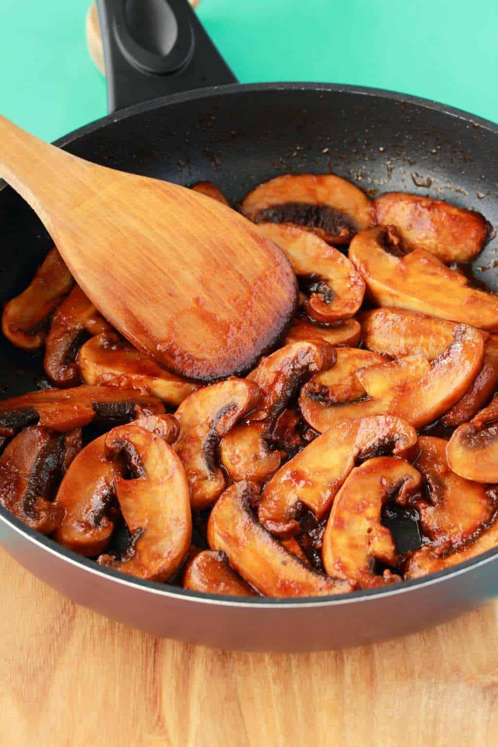 Freshly cooked mushrooms in a frying pan with a wooden spoon.