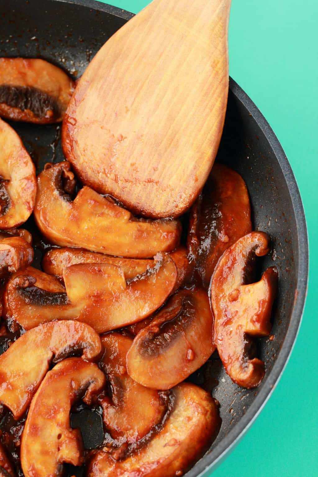 Freshly cooked mushrooms in a frying pan with a wooden spoon in the pan.